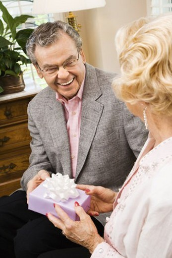 Mature Caucasian man giving present to mature Caucasian woman. : Stock Photo