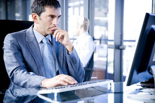 Businessman sat at a desk using a computer looking stressed : Stock Photo
