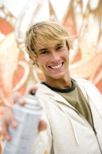 Stock Photo: 4029R-288780 Portrait of a young man holding a spray can in front of a wall covered in graffiti