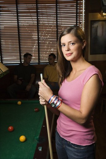 Portrait of woman standing by billiards table holding pool stick. : Stock Photo
