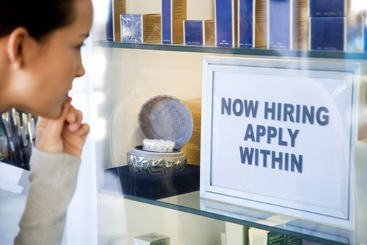 Woman looking at job advert in shop window : Stock Photo