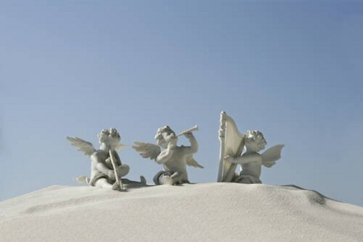 Angel figurines with musical instruments on white sand : Stock Photo