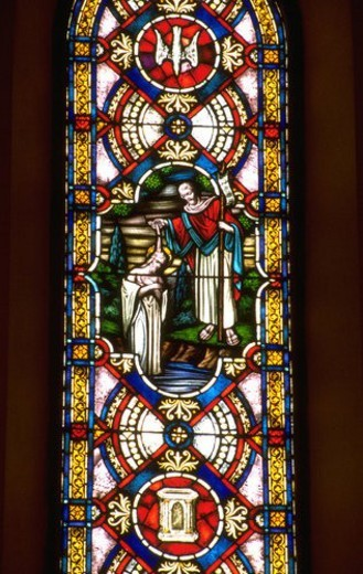 Stained glass window of John the Baptist baptizing Jesus in the river : Stock Photo