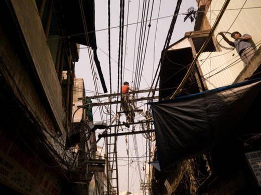 Repairmen working on overhead wires in Delhi India : Stock Photo