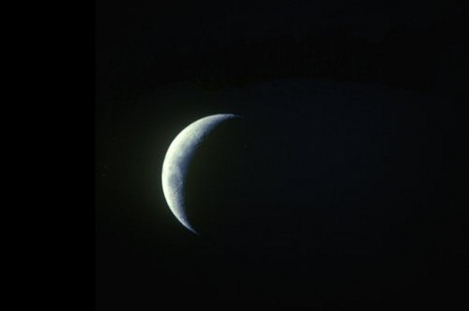A crescent moon against a black starless sky : Stock Photo