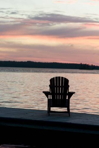 Lake of the Woods, Ontario, Canada; Empty deck chair on a pier next to a lake : Stock Photo