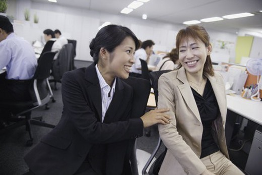 A woman sharing a joke with her colleague in the office : Stock Photo
