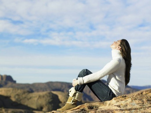 Young woman sitting on rocky hill : Stock Photo