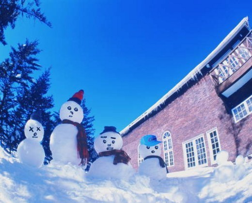 Snowman family outside in the yard : Stock Photo