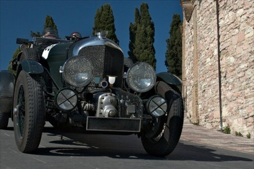 Low front-side view of green antique Bentley  with driver and passenger, showing head lamps, grille and wheels, on road in Assisi, at Mille Miglia, with blue sky and cypress trees in background : Stock Photo