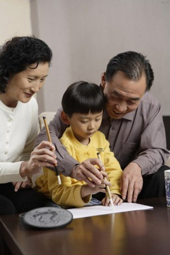 Grandfather and Grandmother practising Chinese calligraphy with grandson : Stock Photo