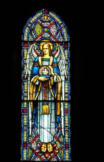 Angel holding religious symbol stained glass window : Stock Photo