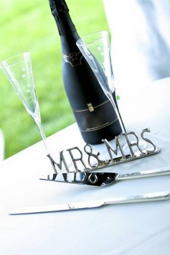 Chrome  Mr & Mrs  sign next to champagne and cake server : Stock Photo