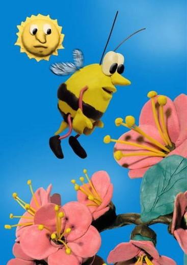 Bee buzzing around flowers : Stock Photo