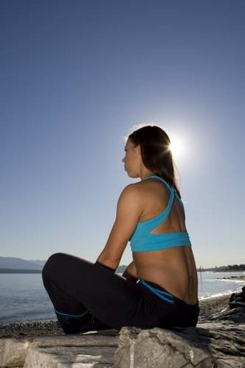 Girl doing yoga on the beach at Spanish Banks park in Vancouver, British Columbia. : Stock Photo