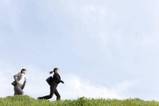Businesswomen running on grass : Stock Photo