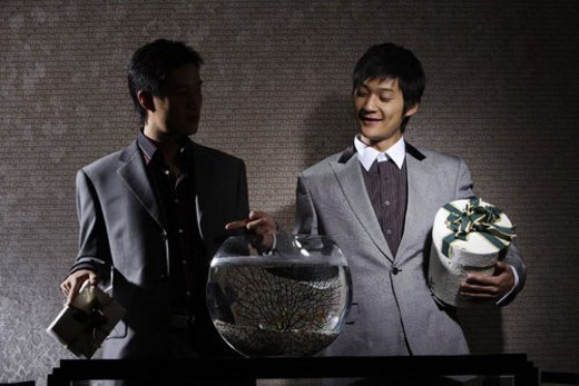 Young men in suit holding boxes of gift with a fishbowl in front : Stock Photo