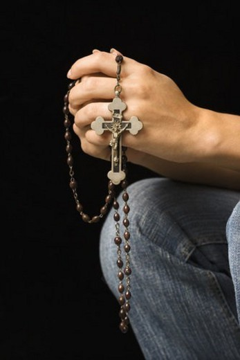 Stock Photo: 4029R-30692 Woman s hands holding rosary with crucifix.
