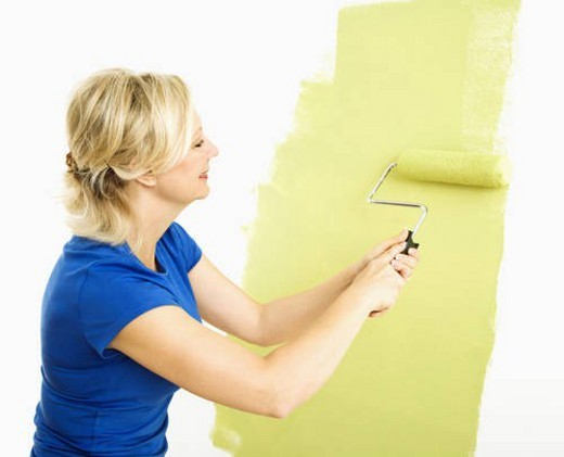 Middle-aged woman painting wall green with paint roller. : Stock Photo