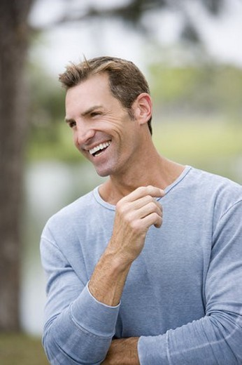 mid adult man laughing standing in garden : Stock Photo