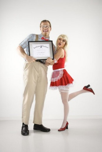 Caucasian young man dressed like nerd holding certificate with Caucasian young blonde woman dressed in french maid outfit. : Stock Photo
