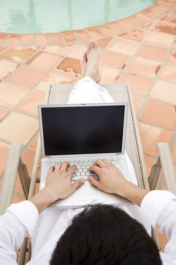 Man using a laptop by the pool : Stock Photo