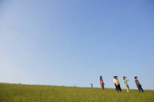Five friends standing in a field : Stock Photo