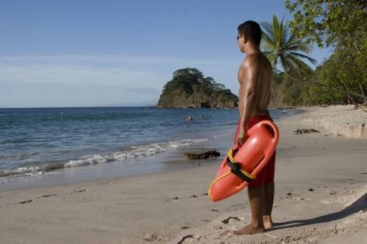 life guard on duty. male holding a life rescue safety floatation device while watching people swimming in the ocean : Stock Photo