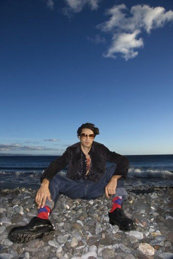 Stock Photo: 4029R-315179 Caucasian young adult male sitting on rocky beach.