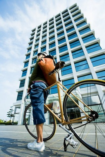 The Messenger On A Bicycle In Front Of A Building : Stock Photo