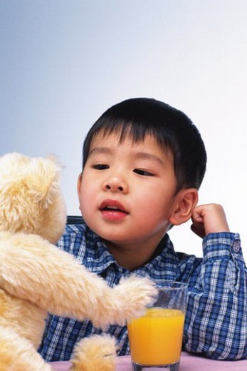 Little Boy playing with a teddy bear, While Drinking a Glass of Orange Juice, Front View : Stock Photo