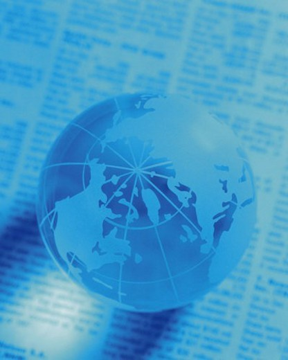 Stock Photo: 4029R-315792 Globe on newspaper, high angle view, close up, soft focus, toned image