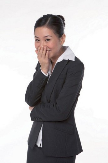 Young woman in business suit, covering mouth with hand, laughing : Stock Photo
