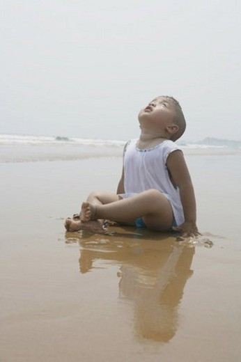 Boy sitting on beach : Stock Photo