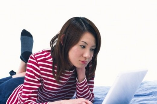 Young Adult Woman Operating a Laptop, Side View, Low Angle View : Stock Photo