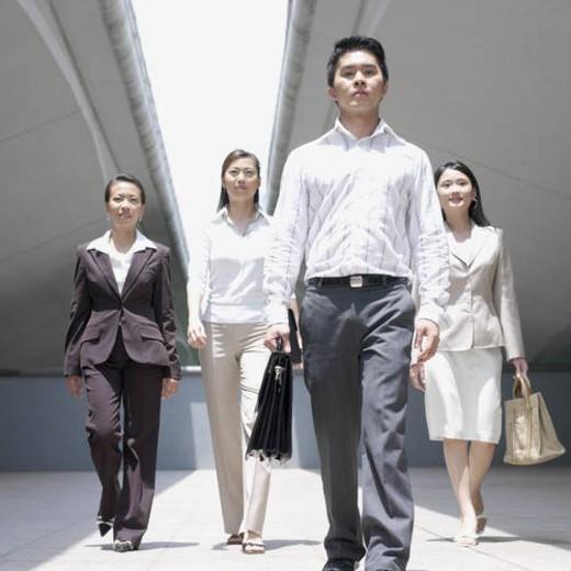 Portrait of a businessman walking with three businesswomen : Stock Photo