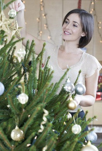 A woman decorating a Christmas tree : Stock Photo