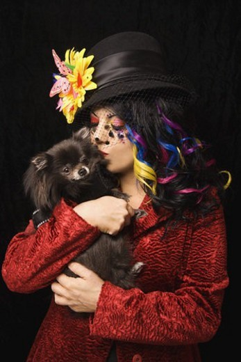 Caucasian woman in unique makeup and clothing holding and kissing black Pomeranian dog standing against black background. : Stock Photo