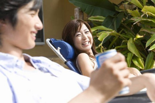 Young couple relaxing at balcony, Saipan, Differential Focus : Stock Photo
