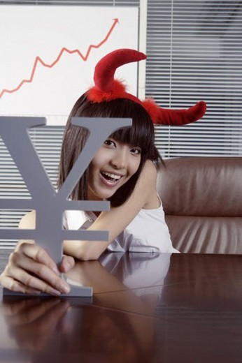 Young woman wearing two red horn, holding RMB symbol : Stock Photo