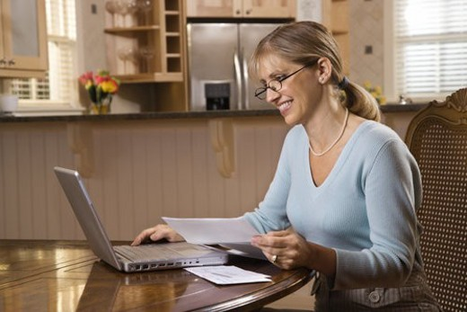 Caucasian mid-adult woman paying bills on laptop computer. : Stock Photo