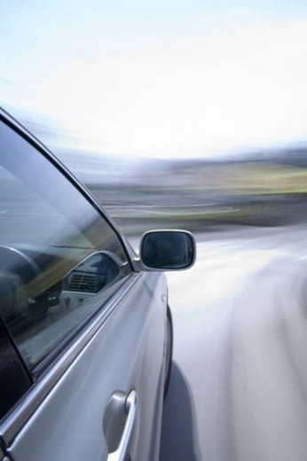 Car driving around a bend in the road : Stock Photo
