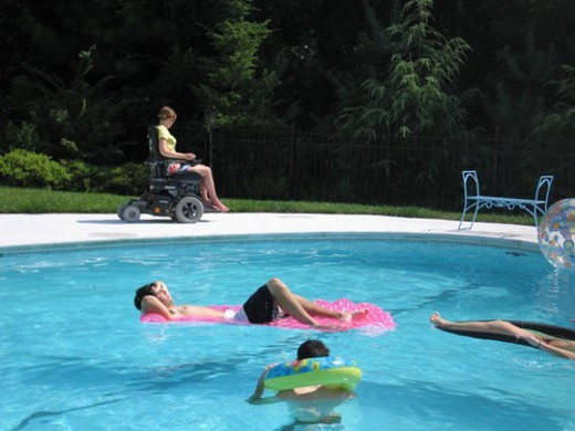 Young woman uses an electric wheelchair to join her family for fun in their accessible pool. : Stock Photo