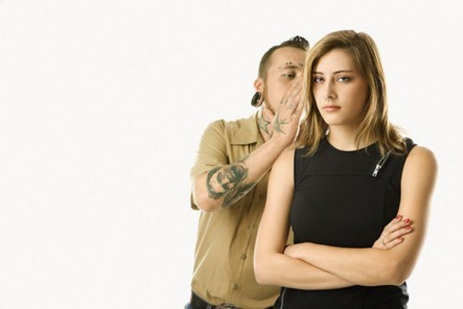 Stock Photo: 4029R-329132 Caucasian mid-adult man whispering into ear of teen female.