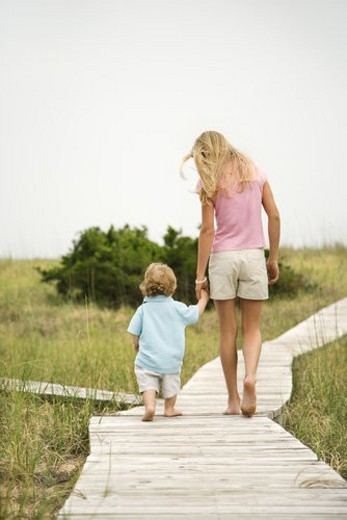Caucasian pre-teen girl walking on beach access walkway and holding hands with Caucasian male toddler . : Stock Photo