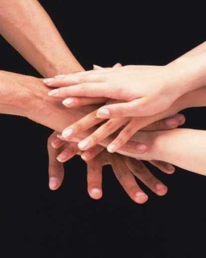 Three people piling hands : Stock Photo