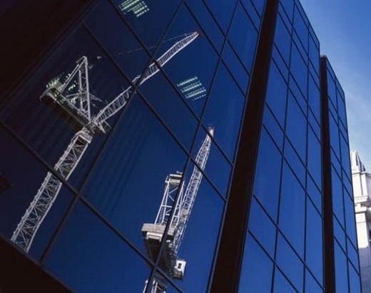 Lattice boom cranes reflected in modern glass facade. : Stock Photo