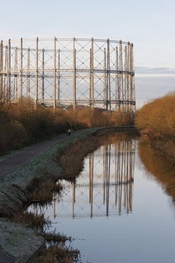 Empty oil or gas  storage tanks in Glasgow Scotland, with circular girder frame reflected in river, on early frosty morning : Stock Photo