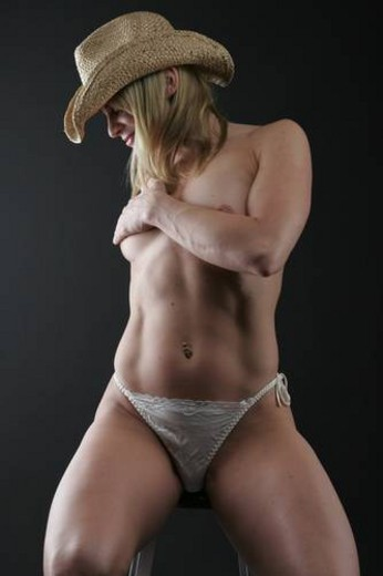 Naked fit girl with cowboy hat covering her body up : Stock Photo