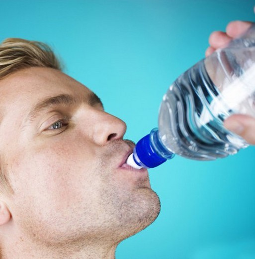 A young man drinking water from a bottle : Stock Photo